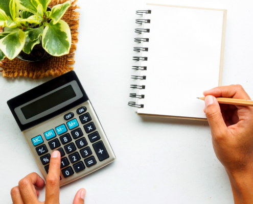 uma mão digitando na calculadora e outra anotando no caderno