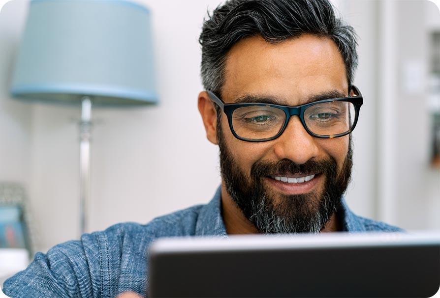 Homem sorrindo e olhando para um notebook
