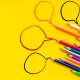 lápis de cor e balões redondos na diagonal sobre fundo amarelo