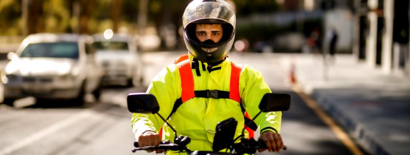 motoboy com capacete digirindo uma moto na rua