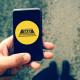 Uma mão segura um celular aberto em um aplicativo de táxi.