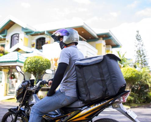 Motoboy em sua moto carregando uma bag nas costas