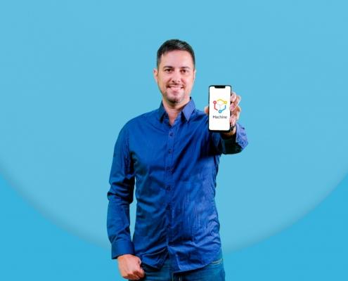Foto do influenciador Fernando Floripa com uma blusa azul e segurando um celular aberto com a logo da Machine na tela.