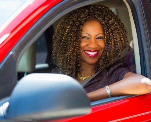 Mulher sorrindo dentro de veículo