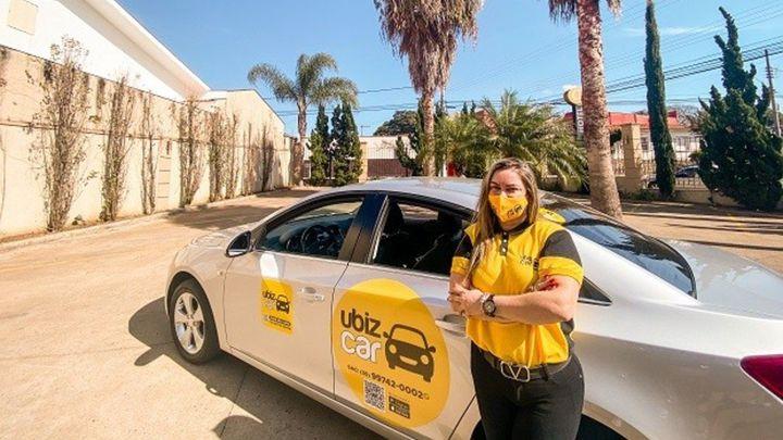 A motorista pousando ao lado de seu carro adesivado com a marca da Ubiz Car
